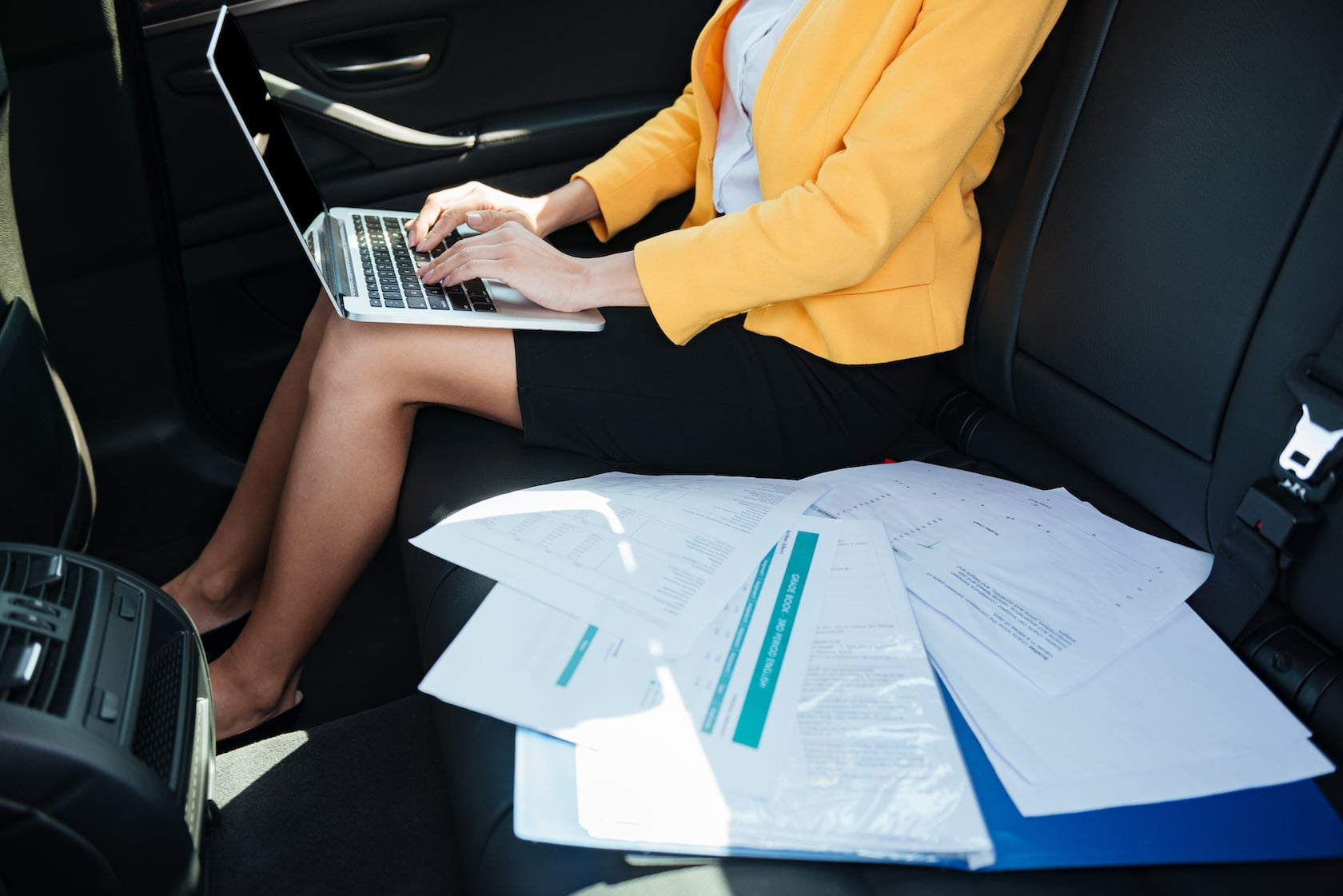 Business woman working on her laptop inside Upper Travel's luxury vehicles in Athens.