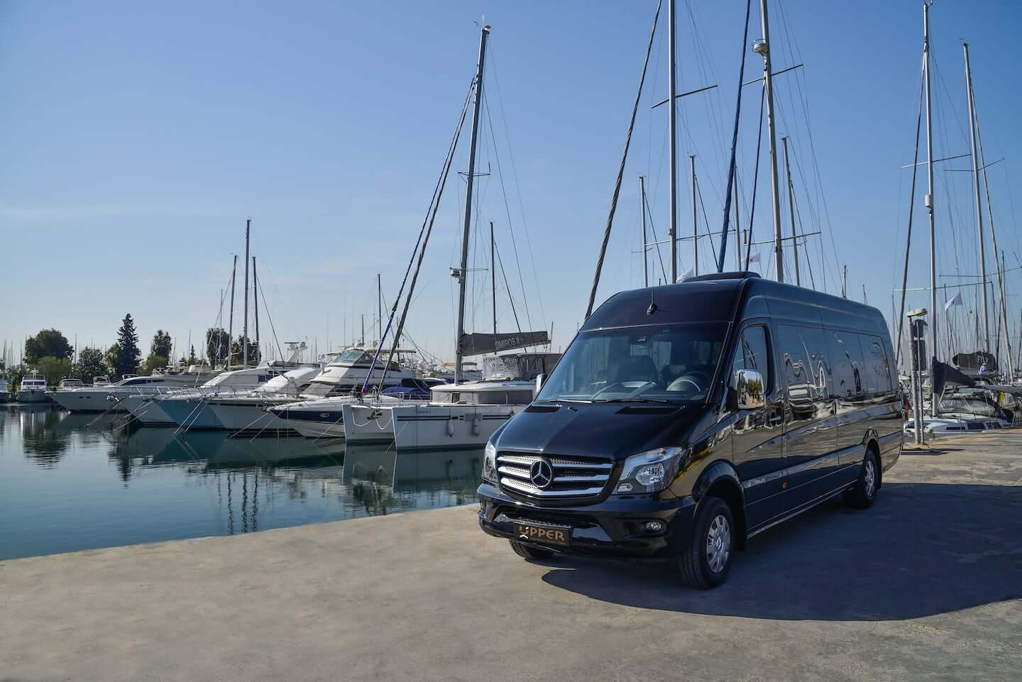 Upper Travel Mercedes-Benz Sprinter Black Tourer, 11 seats parked at the yacht marina.