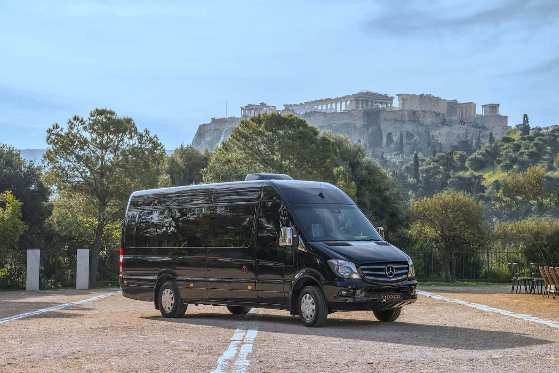 Upper Travel Mercedes-Benz Sprinter Black Avantgarde, 20 seats parked. Acropolis in the back.