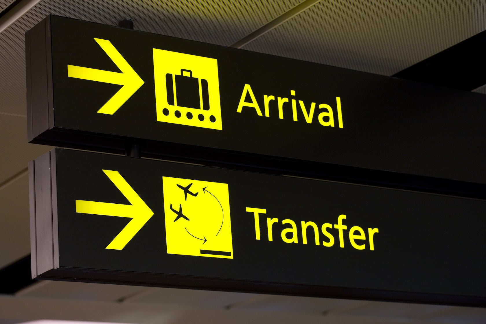 The arrival and transfer signs of an airport. Yellow fonts written against a black surface.