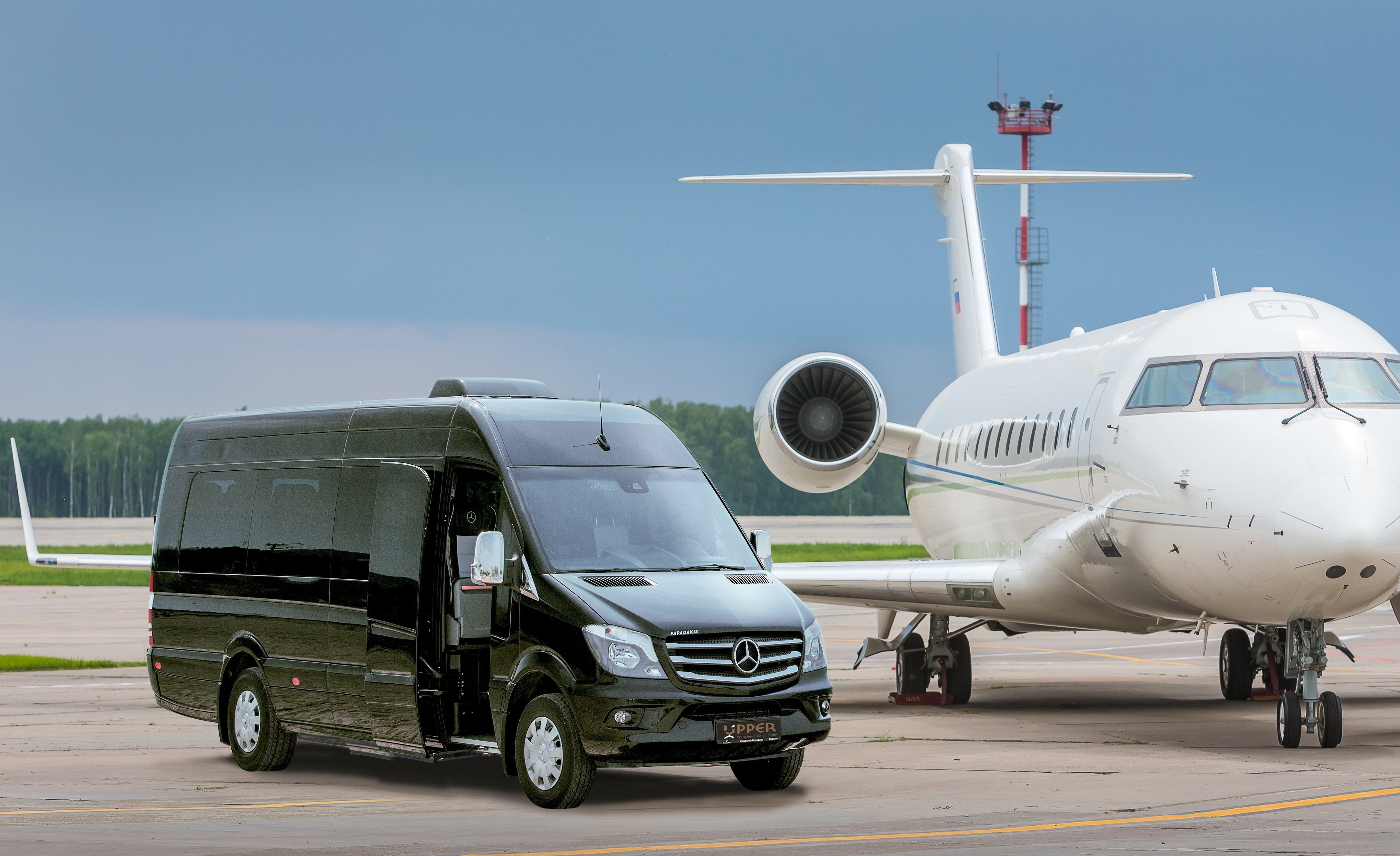 Upper Travel Mercedes-Benz Sprinter Black Avangarde, 22 seats parked by a private jet.