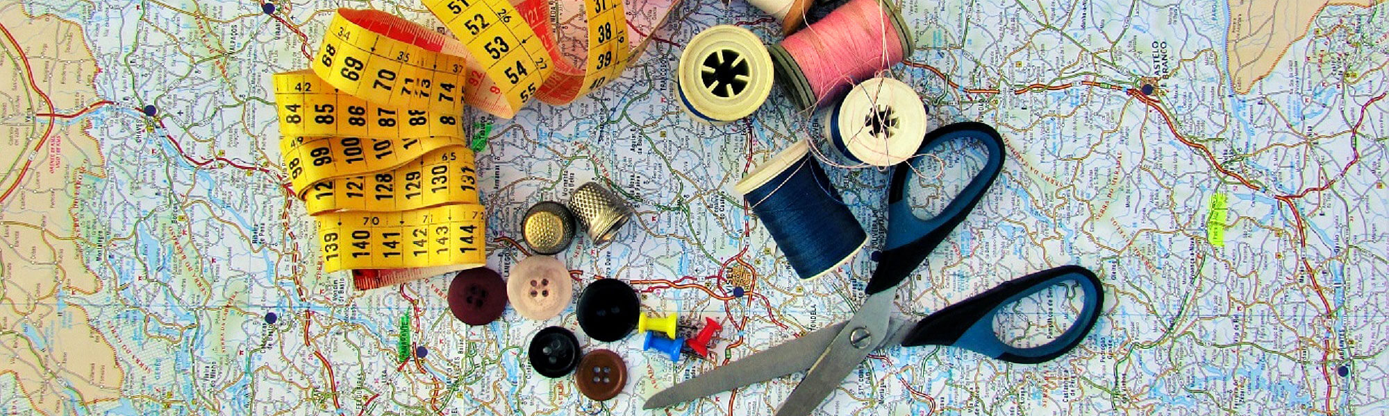 A map, a pair of scissors, buttons, a sewing kit, a thimble, a ruler and pins.